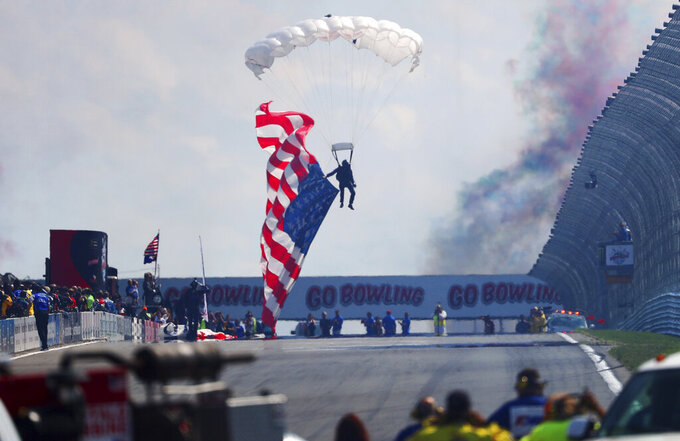 A parachute jumper lands with a large American flag before the start of a NASCAR Cup Series auto race at Watkins Glen International, Sunday, Aug. 4, 2019, in Watkins Glen, N.Y. (AP Photo/John Munson)
