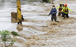 Rescuers wade through a flooded road after the passing of Hurricane Iota in La Lima, Honduras, Wednesday, Nov. 18, 2020. Iota flooded stretches of Honduras still underwater from Hurricane Eta, after it hit Nicaragua Monday evening as a Category 4 hurricane and weakened as it moved across Central America, dissipating over El Salvador early Wednesday. (AP Photo/Delmer Martinez)