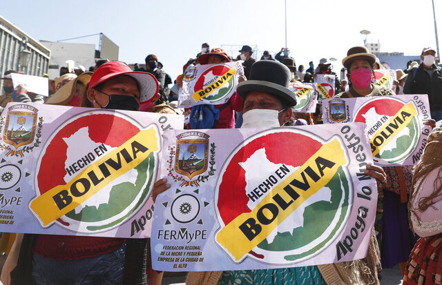 Demonstrators wearing masks amid the new coronavirus pandemic protest demanding that the government authorize the reopening of small businesses, in La Paz, Bolivia, Wednesday, June 17, 2020. (AP Photo/Juan Karita)