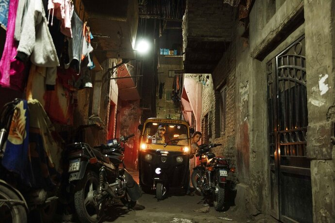 In this Nov. 19, 2019 photo, a driver tries to maneuver his tuk-tuk in a narrow alleyway of a slum in Cairo, Egypt. Motorized rickshaws known as tuk-tuks have ruled the streets of Cairo's slums for the past two decades hauling millions of Egyptians home every day. Now the government is taking its most ambitious stand yet against the polluting three-wheeled vehicles: to modernize the neglected transport system, it plans to replace tuk-tuks with clean-running minivans. (AP Photo/Nariman El-Mofty)