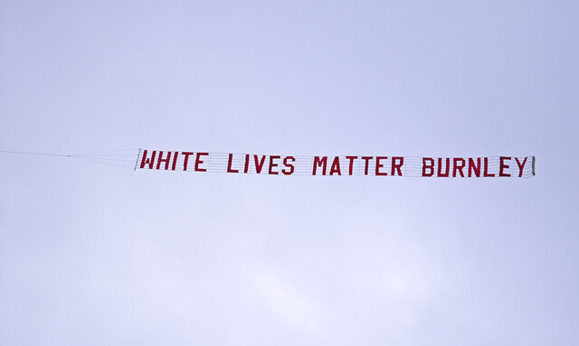 A plane towing a banner reading White Lives Matter Burnley flies above the stadium during the during the English Premier League soccer match between Manchester City and Burnley at Etihad Stadium, in Manchester, England, Monday, June 22, 2020. (AP Photo/Shaun Botterill,Pool)