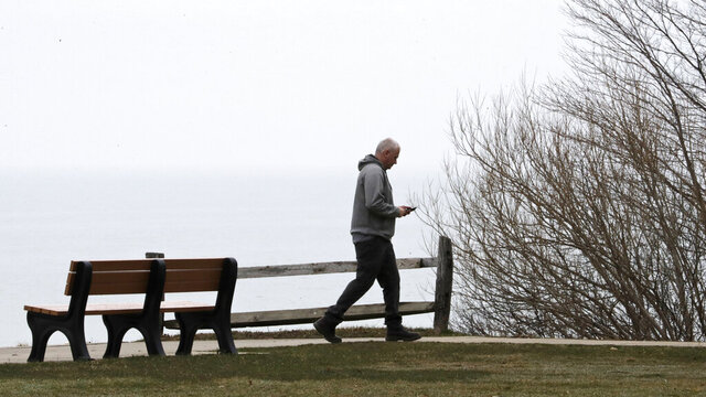 A man walks along the shores of Lake Erie at Sims Park during the coronavirus outbreak, Thursday, March 19, 2020, in Euclid, Ohio. For most people, the virus causes only mild or moderate symptoms, such as fever and cough. For some, especially older adults and people with existing health problems, it can cause more severe illness, including pneumonia, or death.  (AP Photo/Tony Dejak)
