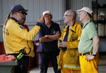 Volunteer firefighters discuss their planned defense against the fire near Towamba, Australia, Friday, Jan. 10, 2020. The wildfires have destroyed more than 2,000 homes and continue to burn, threatening to flare up again as temperatures rise. (AP Photo/Rick Rycroft)