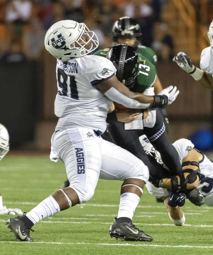 Utah State defensive end Devon Anderson (91) and his teammate safety Gaje Ferguson, bottom right, sack Hawaii quarterback Cole McDonald (13) in the first half of an NCAA college football game, Saturday, Nov. 3, 2018, in Honolulu. (AP Photo/Eugene Tanner)