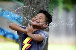 "Byron Xol, an immigrant from Guatemala, squeezes a water balloon during his birthday party Sunday, June 23, 2019, in Buda, Texas. ""Super good!"" the 9-year-old yelled, again and again as they burst. (AP Photo/David J. Phillip)"