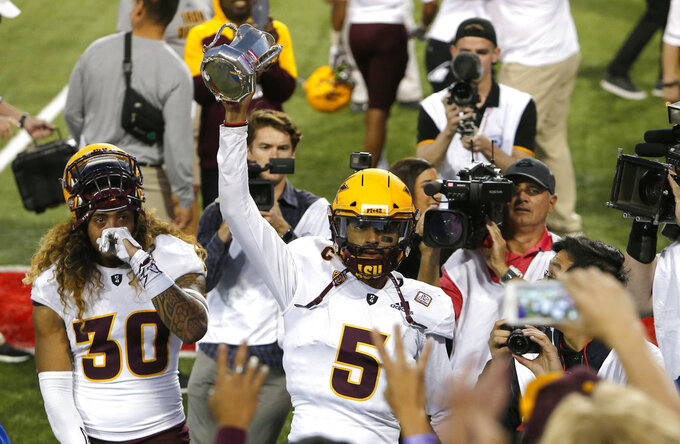 Arizona State quarterback Manny Wilkins (5) celebrates with fans by holding up the Territorial Cup after defeating Arizona in an NCAA college football game, Saturday, Nov. 24, 2018, in Tucson, Ariz. (AP Photo/Rick Scuteri)
