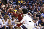 Oklahoma forward Kristian Doolittle (21) looks to pass the ball while defended by West Virginia guard Miles McBride (4) during the first half of an NCAA college basketball game Saturday, Feb. 29, 2020, in Morgantown, W.Va. (AP Photo/Kathleen Batten)