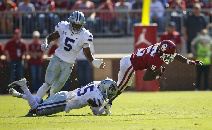 Oklahoma wide receiver Marquise Brown, right, is tackled by Kansas State defensive back Walter Neil Jr. (15) in the first half of an NCAA college football game in Norman, Okla., Saturday, Oct. 27, 2018. Kansas State linebacker Da'Quan Patton back left, looks on. (AP Photo/Sue Ogrocki)