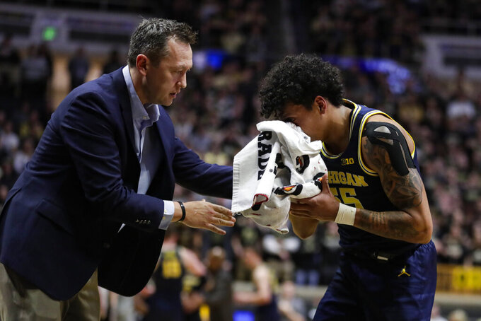 Michigan guard Eli Brooks (55) is assisted after being injured during the second half of an NCAA college basketball game against Purdue in West Lafayette, Ind., Saturday, Feb. 22, 2020. (AP Photo/Michael Conroy)