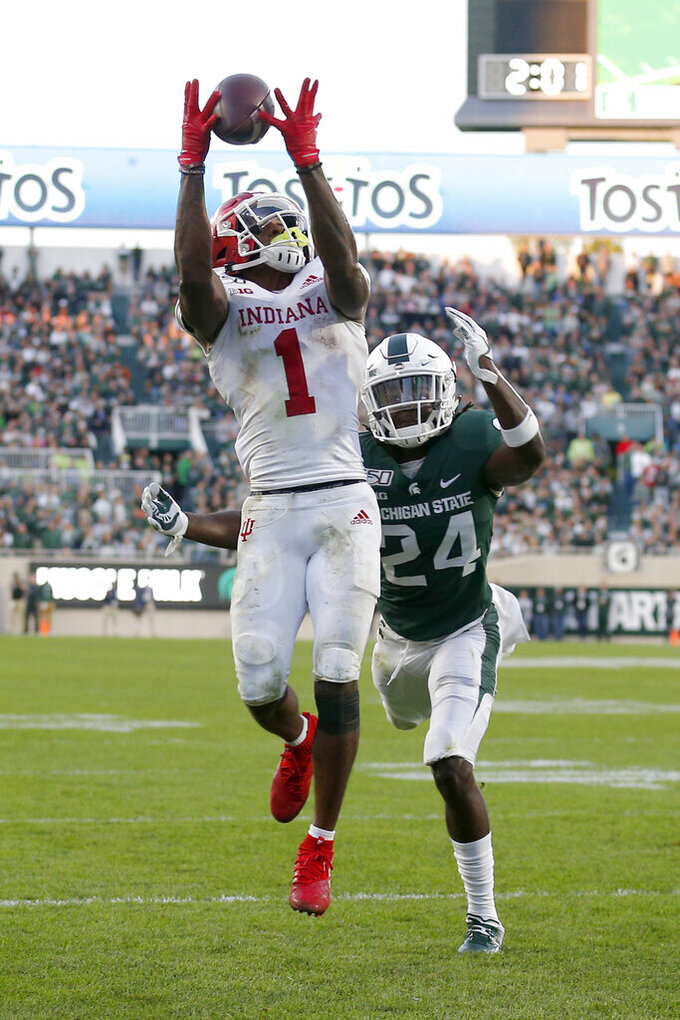 Indiana's Whop Philyor (1) catches a pass for a touchdown against Michigan State's Tre Person (24) during the fourth quarter of an NCAA college football game, Saturday, Sept. 28, 2019, in East Lansing, Mich. (AP Photo/Al Goldis)