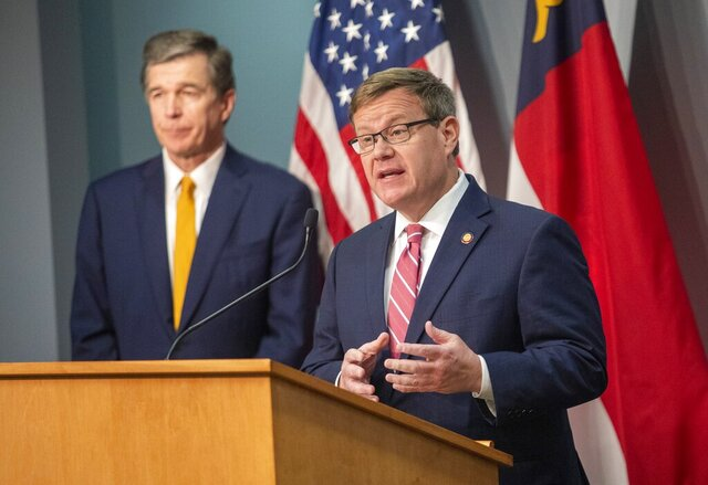 House Speaker Tim Moore speaks as Gov. Roy Cooper looks on during a briefing on North Carolina's coronavirus pandemic response Monday, May 4, 2020 at the NC Emergency Operations Center in Raleigh.(Travis Long/The News & Observer via AP)
