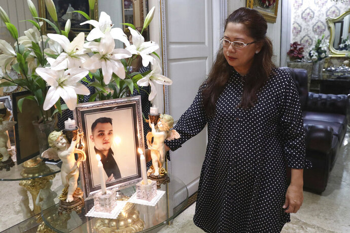 Herlina Simbala looks at a portrait of her son, Dr. Michael Robert Marampe during an online memorial service to mark the 40th day since Marampe passed away due to COVID-19 in Jakarta, Indonesia, on June 5, 2020. Marampe knew what he wanted to be since he was a kid: a doctor and a pianist. He became both, and his passion for music even led him to Tri Novia Septiani - a woman he never got to marry because he got the coronavirus. Marampe became one of dozens of doctors the coronavirus has claimed so far in Indonesia. (AP Photo/Tatan Syuflana)