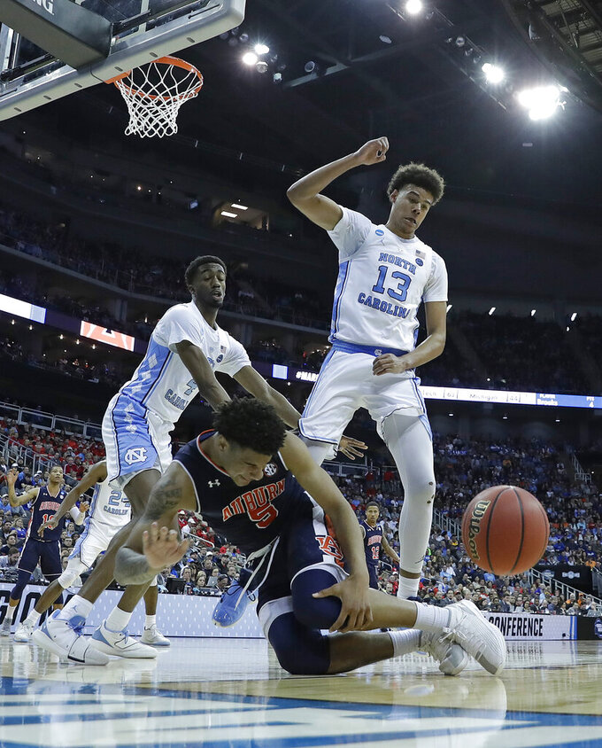 Auburn's Chuma Okeke (5) grabs his leg as he loses control of the ball on his way to the basket as North Carolina's Cameron Johnson (13) and North Carolina's Brandon Robinson, left, defend during the second half of a men's NCAA tournament college basketball Midwest Regional semifinal game Friday, March 29, 2019, in Kansas City, Mo. Okeke was injured on the play. (AP Photo/Charlie Riedel)