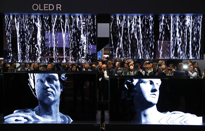 People take pictures of a display of LG Signature OLED R TVs at the LG booth during the CES tech show, Tuesday, Jan. 7, 2020, in Las Vegas. (AP Photo/John Locher)