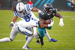 Jacksonville Jaguars running back Ryquell Armstead (23) is stopped by Indianapolis Colts safety Clayton Geathers (26) and cornerback Pierre Desir, lower left, after a run during the first half of an NFL football game, Sunday, Dec. 29, 2019, in Jacksonville, Fla. (AP Photo/Stephen B. Morton)