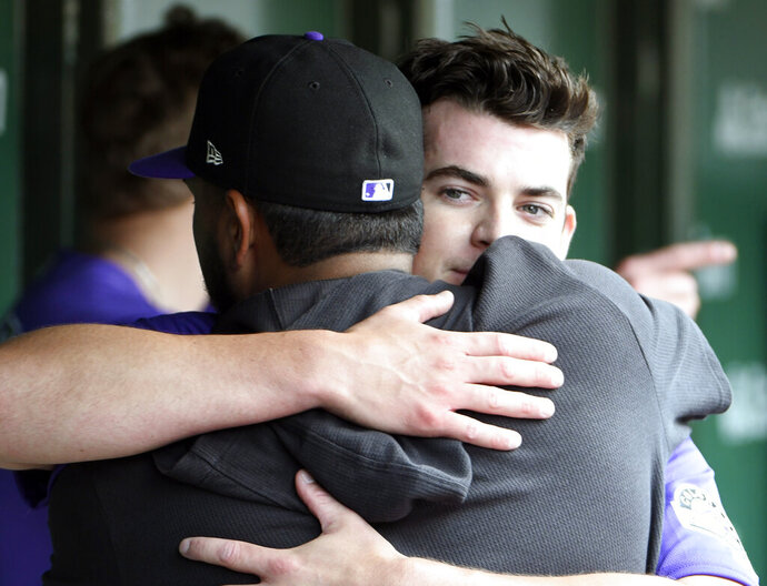 Colorado Rockies starting pitcher Peter Lambert, back, gets hug from Colorado Rockies starting pitcher German Marquez (48), front, in the dugout after completing the seventh inning of a baseball game against the Chicago Cubs, Thursday, June, 6, 2019, in Chicago. (AP Photo/David Banks)