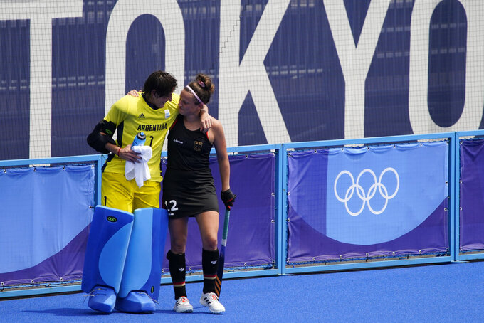 FILE - In this Aug. 2, 2021, file photo, Argentina goalkeeper Maria Belen Succi (1) comforts Germany's Charlotte Stapenhorst, right, after Argentina won their women's field hockey match at the 2020 Summer Olympics, in Tokyo, Japan. In an extraordinary Olympic Games where mental health has been front and center, acts of kindness are everywhere. The world's most competitive athletes have been captured showing gentleness and warmth to one another — celebrating, pep-talking, wiping away each another's tears of disappointment.  (AP Photo/John Locher, File)