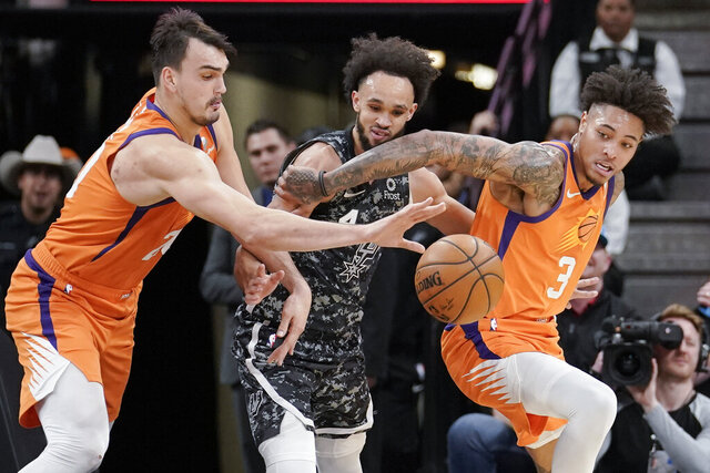Phoenix Suns' Dario Saric, left, and Kelly Oubre, Jr. (3) fight for possession against San Antonio Spurs' Derrick White during the first half of an NBA basketball game, Friday, Jan. 24, 2020, in San Antonio. (AP Photo/Darren Abate)