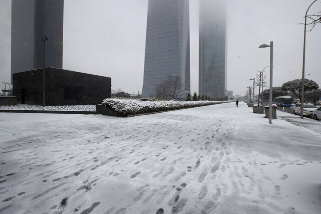 A jogger runs in the business district during a snowfall in Madrid, Spain, Friday, Jan. 8, 2021. Spain is on high alert Friday as a cold snap is covering much of the country with snow, causing disruptions in road, sea and air traffic while authorities warn that the worst may still be coming over the weekend. (AP Photo/Paul White)