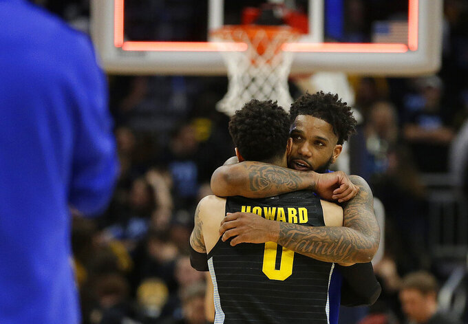 FILE - In this Feb. 29, 2020, file photo, Seton Hall's Myles Powell hugs Marquette's Markus Howard (0) after an NCAA college basketball game in Milwaukee. Powell and Howard went head to head during the regular season in a pair of games befitting two of college basketball's most dynamic players. The potential for a third meeting washed away with the cancellation of the Big East tournament, then NCAA tournament. (AP Photo/Aaron Gash, File)