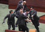 Pro-democracy lawmaker Ted Hui, center, struggles with security personnel at the main chamber of the Legislative Council during the second day of debate on a bill that would criminalize insulting or abusing the Chinese anthem in Hong Kong, Thursday, May 28, 2020. A longer suspension followed the ejection of Ted Hui, who kicked the plastic bottle toward the president's dais after security officers tussled with him and it fell from his hands. (AP Photo)