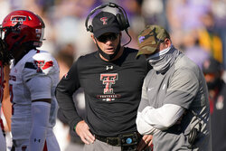 Kansas State coach Chris Klieman, right, and Texas Tech coach Matt Wells talk during a timeout for an injury during the second half of an NCAA college football game Saturday, Oct. 3, 2020, in Manhattan, Kan. (AP Photo/Charlie Riedel)