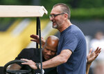 FILE - In this May 31, 2018, file photo, injured Pittsburgh Steelers linebacker Ryan Shazier, left, and former Steelers lineman and current broadcaster, Tunch Ilkin, embrace at an NFL football practice in Pittsburgh. Ilkin, a Turkis-born two-time Pro Bowl offensive lineman with the Pittsburgh Steelers in the 1980s who went on to become a beloved member of the organization's broadcast team, died on Saturday morning, Sept. 4, 2021, the team said. He was 63. Ilkin, who revealed last fall he was fighting amyotrophic lateral sclerosis (also known as Lou Gehrig's Disease), had been hospitalized recently with pneumonia. (AP Photo/Keith Srakocic, File)