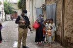A police officer stand guard while a healthcare worker administers a polio vaccine to a child in Peshawar, Pakistan, Friday, July 30, 2021. The Pakistani government launched an anti-polio vaccination campaign in an effort to eradicate the crippling disease. (AP Photo/Muhammad Sajjad)