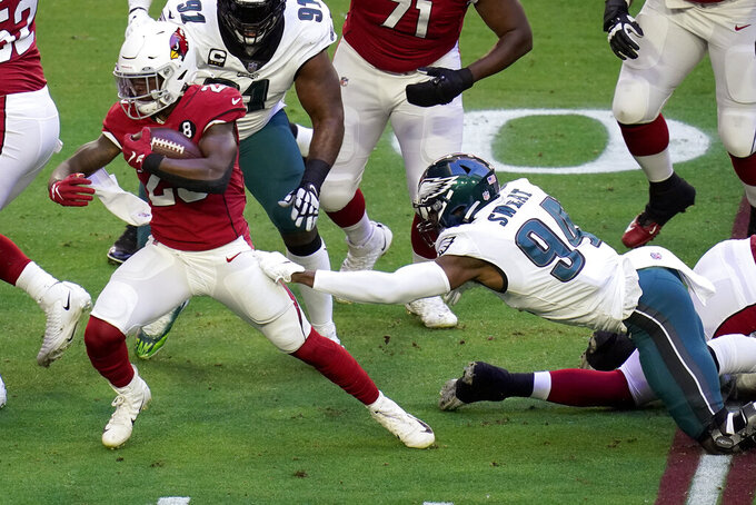 Arizona Cardinals running back Chase Edmonds (29) escapes the grasp of Philadelphia Eagles defensive end Josh Sweat (94) during the first half of an NFL football game, Sunday, Dec. 20, 2020, in Glendale, Ariz. (AP Photo/Ross D. Franklin)