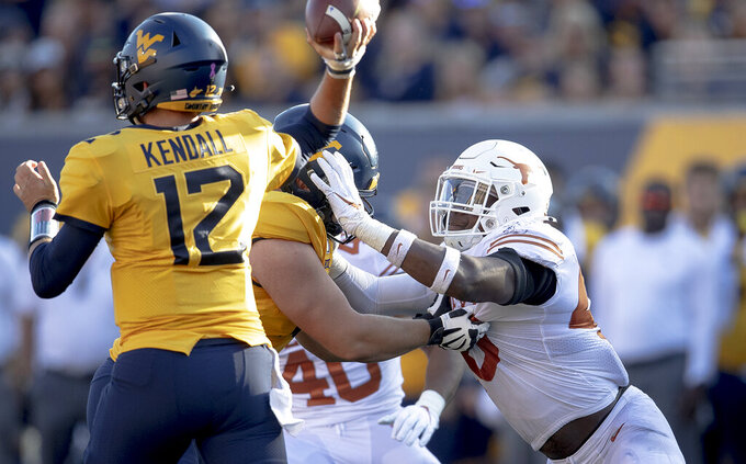 Texas linebacker Joseph Ossai (46) pressures West Virginia quarterback Austin Kendall (12) during an NCAA college football game on Saturday, Oct. 5, 2019, in Morgantown, W.Va. (Nick Wagner/Austin American-Statesman via AP)