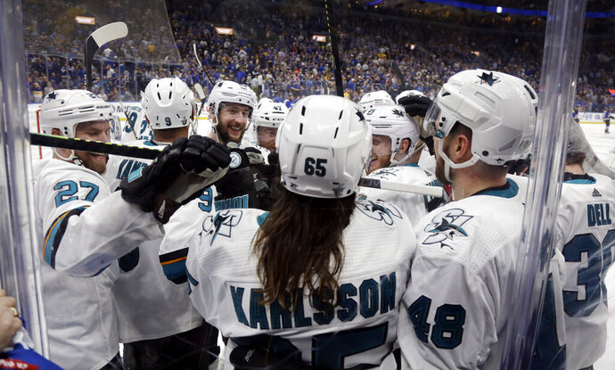 San Jose Sharks defenseman Erik Karlsson (65), of Sweden, is congratulated after scoring the winning goal against the St. Louis Blues during overtime in Game 3 of the NHL hockey Stanley Cup Western Conference final series Wednesday, May 15, 2019, in St. Louis. The Sharks won 5-4 to take a 2-1 lead in the series. (AP Photo/Jeff Roberson)