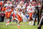 FILE - In this Nov. 30, 2019, file photo, Clemson quarterback Trevor Lawrence (16) carries the ball against South Carolina during the first half of an NCAA college football game, in Columbia, S.C. Heading into this year's slate of conference title games a case could be made that No. 1 LSU (No. 2 CFP), No. 2 Ohio State (No. 1 CFP) and No. 3 Clemson (No. 3 CFP) have all done enough already to lose their conference championship games and still get in the College Football Playoff.(AP Photo/Sean Rayford)