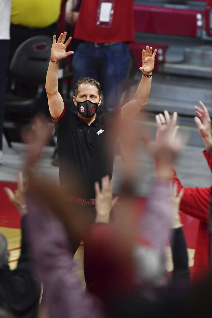 Arkansas coach Eric Musselman calls the hogs with fans after beating Texas A&M during an NCAA college basketball game in Fayetteville, Ark., Saturday, March 6, 2021. (AP Photo/Michael Woods)
