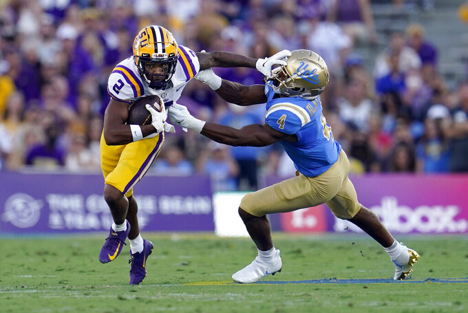 LSU wide receiver Koy Moore (2) stiff-arms UCLA defensive back Stephan Blaylock (4) after a reception during the first half of an NCAA college football game Saturday, Sept. 4, 2021, in Pasadena, Calif. (AP Photo/Marcio Jose Sanchez)