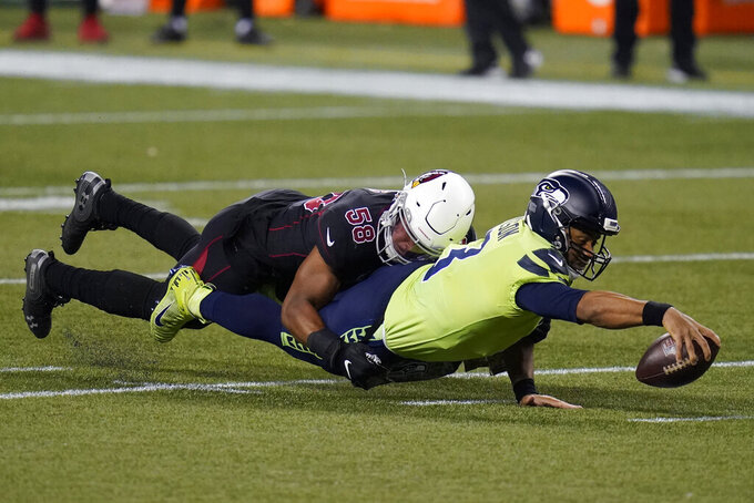 Seattle Seahawks quarterback Russell Wilson reaches for extra yardage as he is tackled by Arizona Cardinals middle linebacker Jordan Hicks (58) during the first half of an NFL football game, Thursday, Nov. 19, 2020, in Seattle. (AP Photo/Elaine Thompson)