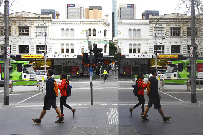 People wearing face masks to help protect against the spread of the new coronavirus walk in the central business district in Melbourne, Australia, Wednesday, July 22, 2020. Australia's hard-hit Victoria state reported a record new COVID-19 cases on Wednesday and health authorities warned that numbers could continue to rise. With Australia's second-largest city Melbourne now in lockdown for two weeks, authorities had hoped the infection rate would begin to plateau. (James Ross/AAP Image via AP)