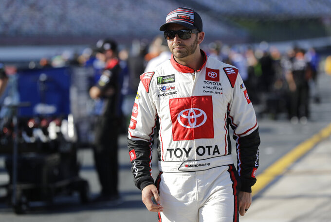 Matt DiBenedetto walks down pit road before qualifying for Saturday's NASCAR All-Star Cup series auto race at Charlotte Motor Speedway in Concord, N.C., Friday, May 17, 2019. (AP Photo/Chuck Burton)