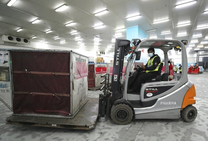 A Pfizer-BioNTech COVID-19 coronavirus vaccine shipment is offloaded into a refrigerated storage space at Dubai International Airport cargo terminal, in Dubai, United Arab Emirates, early Sunday, Feb. 21, 2021. As the coronavirus pandemic continues to clobber the aviation industry, Emirates Airlines, the Middle East's biggest airline is seeking to play a vital role in the global vaccine delivery effort. (AP Photo/Kamran Jebreili)