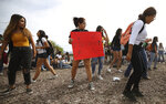 Quiriat Rosas, 17, center with sign, and other students dance to Mexican music after marching from Desert View High School to the Pima County Sheriff's Department on Monday, May 6, 2019 in Tucson, Ariz. Approximately 200 students walked out to protest the detention of their classmate, Thomas Torres, who was stopped by a sheriff's deputy on May 2 and was detained until Border Patrol arrived. (Mamta Popat/Arizona Daily Star via AP)