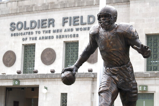 The newly dedicated statue of Chicago Bears and Pro Football Hall of Fame running back Walter Payton stands outside Soldier Field during an unveiling ceremony of statues honoring George Halas and Payton, Tuesday, Sept. 3, 2019, in Chicago. (AP Photo/Charles Rex Arbogast)