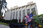 FILE-In this Oct. 27, 2019 file photo a man places an American flag outside the Tree of Life synagogue in Pittsburgh on the first anniversary of the shooting at the synagogue, that killed 11 worshippers. An evidentiary hearing in the case of Robert Bowers a western Pennsylvania truck driver accused of killing 11 people at the Pittsburgh synagogue in 2018, is expected to get underway inside a federal courtroom in Pittsburgh on Tuesday, Oct. 12, 2021. (AP Photo/Gene J. Puskar, File)