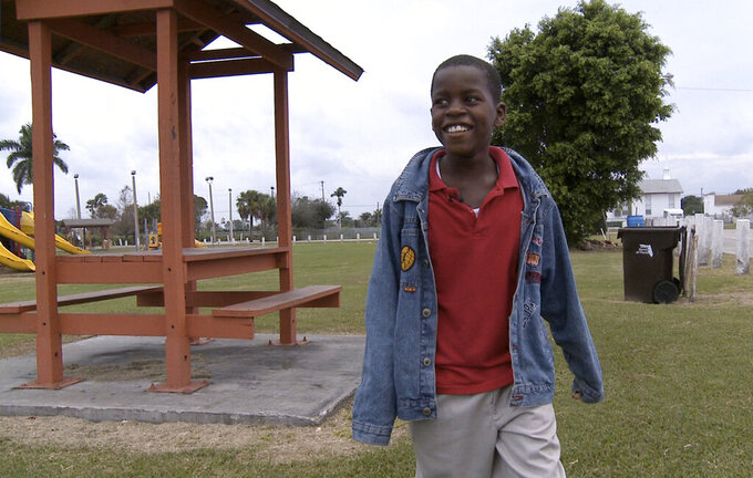 FILE - In this Jan. 13, 2009 file photo, Damon Weaver, 10, walks in a park near his home in Pahokee, Fla. Weaver who gained national acclaim when he interviewed President Barack Obama at the White House in 2009 has died of natural causes, his family says.  Weaver was 23 when he died May 1, 2021 his sister, Candace Hardy, told the Palm Beach Post.   (AP Photo/ Lynne Sladky, File )