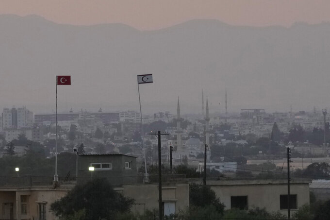 A Turkish military guard post with Turkey's flag, left, and Turkish Cypriot breakaway flag, right, is seen in front of the Famagusta, city, prior the Turkish President visit the Turkish occupied part of the island at the north, in Dherynia, Cyprus, Monday, July 19, 2021. The government of ethnically split Cyprus is protesting to the United Nations and the European Union a decision by Turkey and breakaway Turkish Cypriots to re-open a residential section of an abandoned, military-controlled suburb that it says violates U.N. resolutions and could scupper peace efforts. (AP Photo/Petros Karadjias)