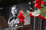 Flowers in front of a photograph of Britain's Prince Philip outside Windsor Castle in Windsor, England after the announcement regarding the death of Britain's Prince Philip, Friday, April 9, 2021. Buckingham Palace officials say Prince Philip, the husband of Queen Elizabeth II, has died. He was 99. Philip spent a month in hospital earlier this year before being released on March 16 to return to Windsor Castle. (AP Photo/Frank Augstein)