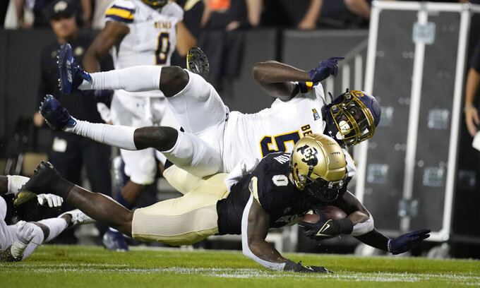 Colorado running back Ashaad Clayton, front, tumbles to the turf after being tripped by Northern Colorado defensive back Komotay Koffie during the second half of an NCAA college football game Friday, Sept. 3, 2021, in Boulder, Colo. Colorado won 35-7. (AP Photo/David Zalubowski)