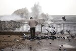 A man feeds pigeons next the breakwater in Barcelona, Spain, Wednesday, Jan. 22, 2020. Massive waves and gale-force winds smashed into seafront towns, damaging many shops and restaurants and flooding some streets. (AP Photo/Joan Mateu)