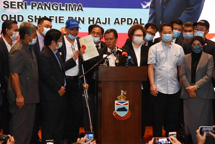 Sabah Chief Minister Shafie Apdal, centre, in Kota Kinabalu, Sabah, Malaysia Thursday, July 30, 2020. Shafie dissolved the state parliament to pave the way for polls after a ruling party politician claimed he had majority support of lawmakers to form a new government. (AP Photo)