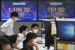 Currency traders watch monitors at the foreign exchange dealing room of the KEB Hana Bank headquarters in Seoul, South Korea, Wednesday, July 8, 2020. Asian shares were mostly lower Wednesday as uncertainty over the pandemic sapped the buying enthusiasm that has been driving prices higher. (AP Photo/Ahn Young-joon)