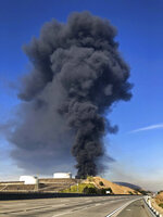 Interstate 80 is closed as a fire at an oil storage facility burns Tuesday, Oct. 15, 2019, in Rodeo, Calif. A fire burning at NuStar Energy LP facility in Crockett, Calif., in the San Francisco Bay Area prompted a hazardous materials emergency that led authorities to order the residents of two communities, including Rodeo, to stay inside with all windows and doors closed. Contra Costa Fire Department spokesman Steve Hill said that an hour into battling the blaze, firefighters seemed to be making progress and were continuing to keep adjacent tanks cooled with water. (AP Photo/Ben Margot)