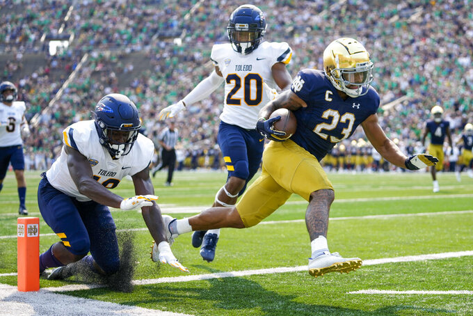 Notre Dame running back Kyren Williams (23) scores a touchdown in front of Toledo's Saeed Holt (20) and Nate Givhan (48) during an NCAA college football game in South Bend, Ind., Saturday, Sept. 11, 2021. (AP Photo/AJ Mast)